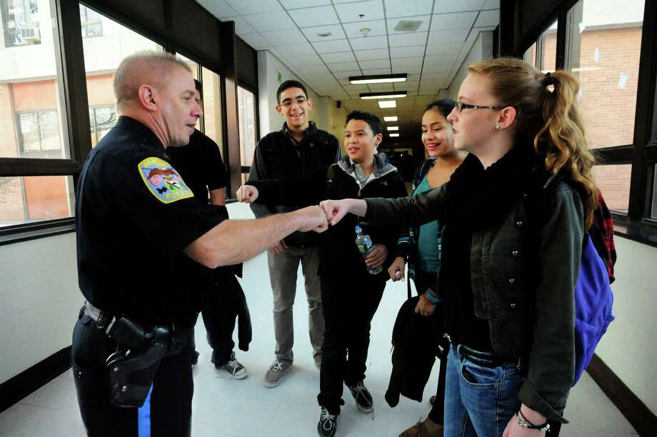 School Resource Officer Brian Hayes greets students, including Kate Jakobson, 14, an eight-grader, right, with a fist bump, at Broadview Middle School in Danbury, Conn. Friday Feb. 15, 2013. Photo: Michael Duffy / The News-Times