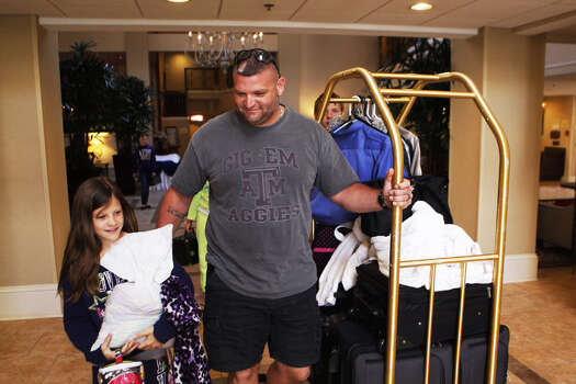 Kenneth Brown Jr. of Texas City walks with his daughter Amber, 11, at their hotel in Mobile, Ala., after Kenneth returned with a rental vehicle to drive his family of six home to Texas City. The family had to sleep outside on an upper deck because sewage and water flooded their room. Photo: Johnny Hanson / Houston Chronicle