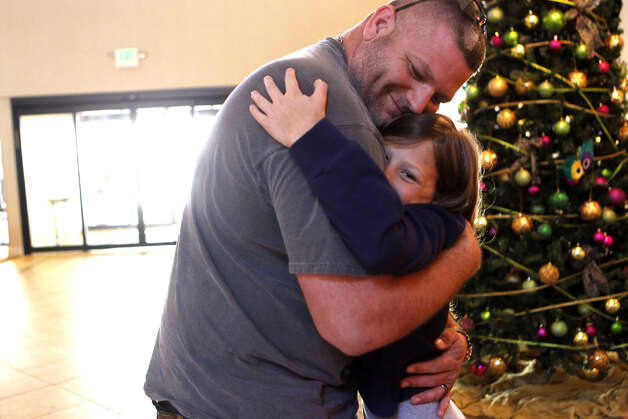 Kenneth Brown Jr. of Texas City hugs his daughter Amber, 11, at their hotel in Mobile, Ala., after Kenneth returned with a rental vehicle to drive his family of six home to Texas City. The family had to sleep outside on an upper deck because sewage and water flooded their room. Photo: Johnny Hanson / Houston Chronicle
