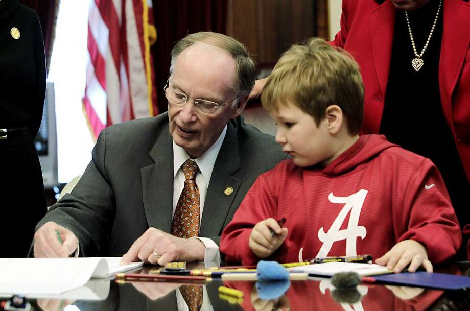 Alabama Gov. Robert Bentley draws with 6-year-old Ethan Gilman during a visit to the governor's office in Montgomery. Photo: Jamie Martin, Associated Press