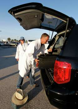David Green, right, of Burleson,Texas, loads his luggage into his car after he and his wife, Katie, left, arrived by bus from Mobile, Ala., where the disabled Carnival ship Triumph docked, on Friday February 15, 2013 in Galveston.  Hundreds of passengers opted to take an eight-hour bus ride to Galveston from Mobile.  Galveston is the home port of the ill-fated ship, which lost power in an engine-room fire Sunday some 150 miles off Mexico's Yucatan peninsula. (AP Photo/The Galveston County Daily News, Jennifer Reynolds)  Photo: Jennifer Reynolds, Associated Press / The Galveston County Daily News