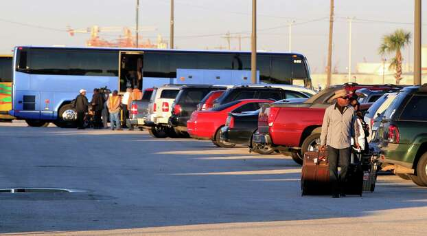 Passengers from the Carnival ship Triumph arrive by bus and some look for their cars at the Port of Galveston parking lot in Galveston, Texas on Friday Feb. 15, 2013.  Hundreds of passengers opted to take an eight-hour bus ride to Galveston from Mobile.  Galveston is the home port of the ill-fated ship, which lost power in an engine-room fire Sunday some 150 miles off Mexico's Yucatan peninsula. (AP Photo/The Galveston County Daily News, Jennifer Reynolds)  Photo: Jennifer Reynolds, Associated Press / The Galveston County Daily News