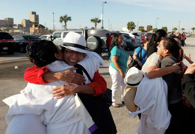 Patricia Wagner, right, hugs her sister Mercedes Perez de Colon,as their group is reunited after taking separate buses from Mobile, Ala., where the disabled Carnival ship Triumph docked, on Friday February 15, 2013 in Galveston, Texas. Hundreds of passengers opted to take an eight-hour bus ride to Galveston from Mobile.  Galveston is the home port of the ill-fated ship, which lost power in an engine-room fire Sunday some 150 miles off Mexico's Yucatan peninsula. (AP Photo/The Galveston County Daily News, Jennifer Reynolds)  Photo: Jennifer Reynolds, Associated Press / The Galveston County Daily News