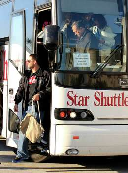 Carnival Triumph cruise ship passengers arrive by bus in Galveston, Texas on Friday Feb. 15, 2013.  Hundreds of passengers opted to take an eight-hour bus ride to Galveston from Mobile.  Galveston is the home port of the ill-fated ship, which lost power in an engine-room fire Sunday some 150 miles off Mexico's Yucatan peninsula. (AP Photo/The Galveston County Daily News, Jennifer Reynolds)  Photo: Jennifer Reynolds, Associated Press / The Galveston County Daily News