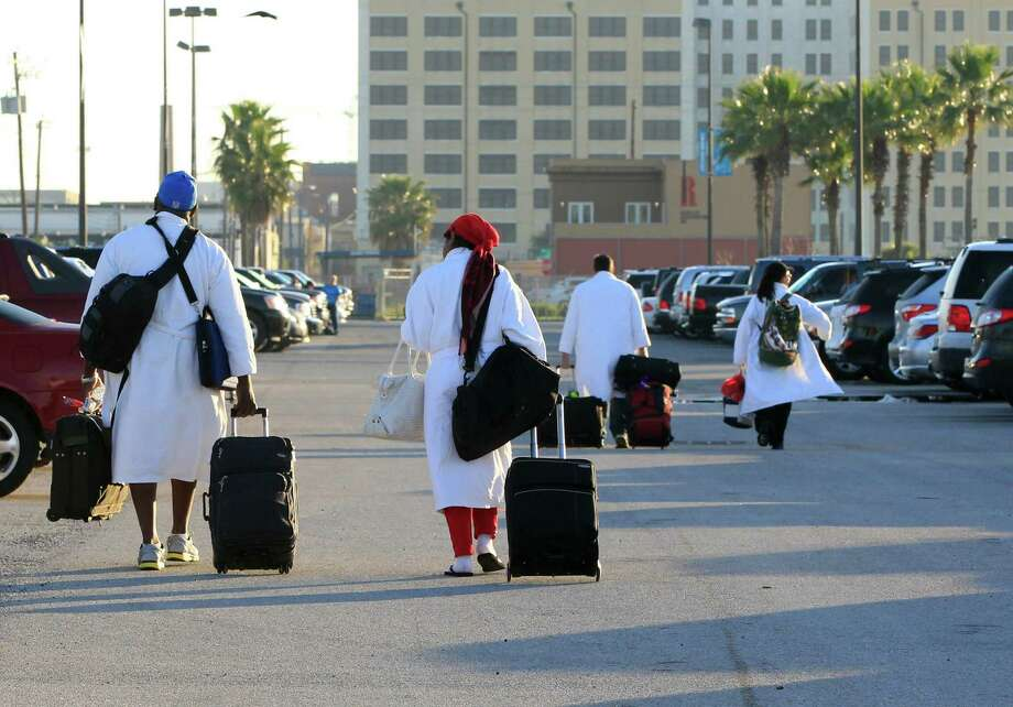 Passengers from the Carnival ship Triumph, all wearing their Carnival bathrobes, head to their cars after arriving in Galveston, Texas from Mobile, Ala.  on Friday Feb. 15, 2013.  Hundreds of passengers opted to take an eight-hour bus ride to Galveston from Mobile.  Galveston is the home port of the ill-fated ship, which lost power in an engine-room fire Sunday some 150 miles off Mexico's Yucatan peninsula. (AP Photo/The Galveston County Daily News, Jennifer Reynolds) Photo: Jennifer Reynolds, Associated Press / The Galveston County Daily News
