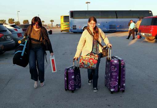 Carnival Triumph passengers Brooke Carico, left, and her daughter, Ravyn, head to their car after arriving by bus at the Port of Galveston, Texas parking lot Friday Feb. 15, 2013.  They were among the first passengers to arrive after an overnight trip from Mobile, Ala., where the disabled Carnival ship Triumph docked.   Hundreds of passengers opted to take an eight-hour bus ride to Galveston from Mobile.  Galveston is the home port of the ill-fated ship, which lost power in an engine-room fire Sunday some 150 miles off Mexico's Yucatan peninsula. (AP Photo/The Galveston County Daily News, Jennifer Reynolds)  Photo: Jennifer Reynolds, Associated Press / The Galveston County Daily News