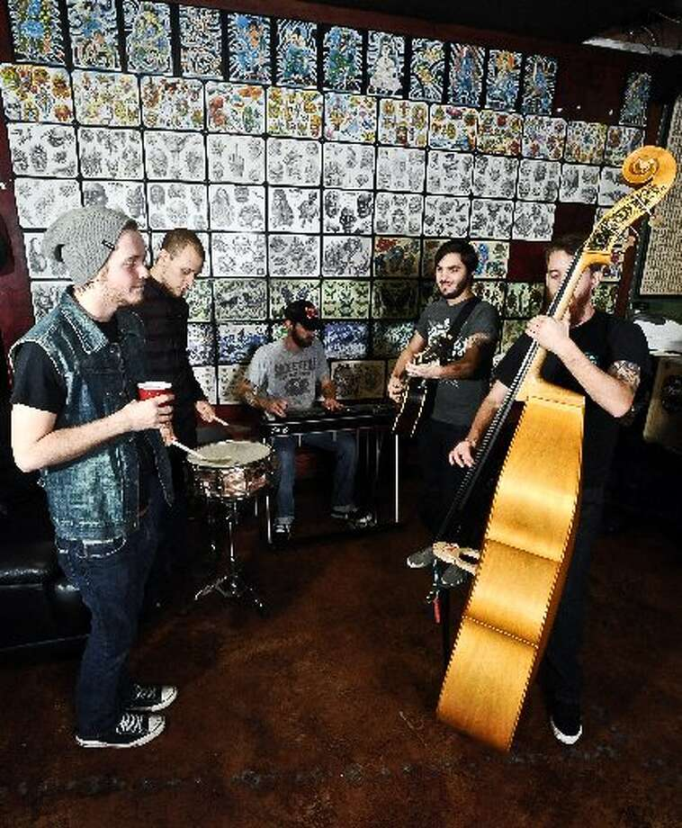 The Ramblin' Boys, from left to right: Bobby Parrott, Patrick Brignac, Alan Rascoe, James Faust, and David Pool jam a few songs at Santa Fe Tattoo Parlor on Calder Avenue in Beaumont. Randy Edwards/cat5