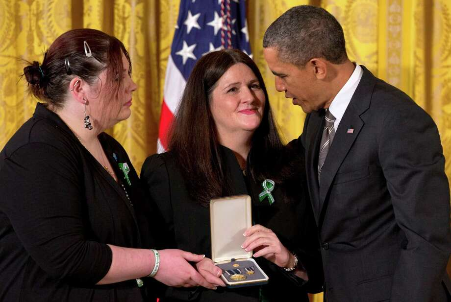 President Barack Obama presents a 2012 Citizens Medal to the family of slain Sandy Hook Elementary School teacher's aide Rachel Davino, Friday, Feb. 15, 2013, in the East Room of the White House in Washington.  (AP Photo/Jacquelyn Martin) Photo: Jacquelyn Martin, STF / AP