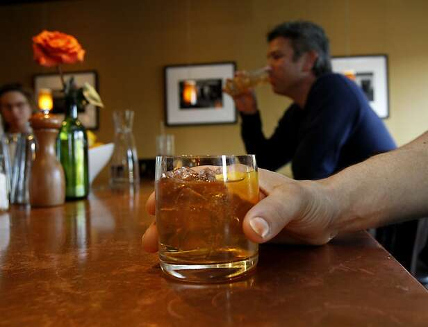 A bourbon on the rocks is served to an unidentified patron on Valentine's Day. Researchers have linked the use of alcohol to cancer. This was not surprising to a group at an upscale bar on Grand Avenue near downtown Oakland Thursday February 14, 2013. Photo: Brant Ward, The Chronicle
