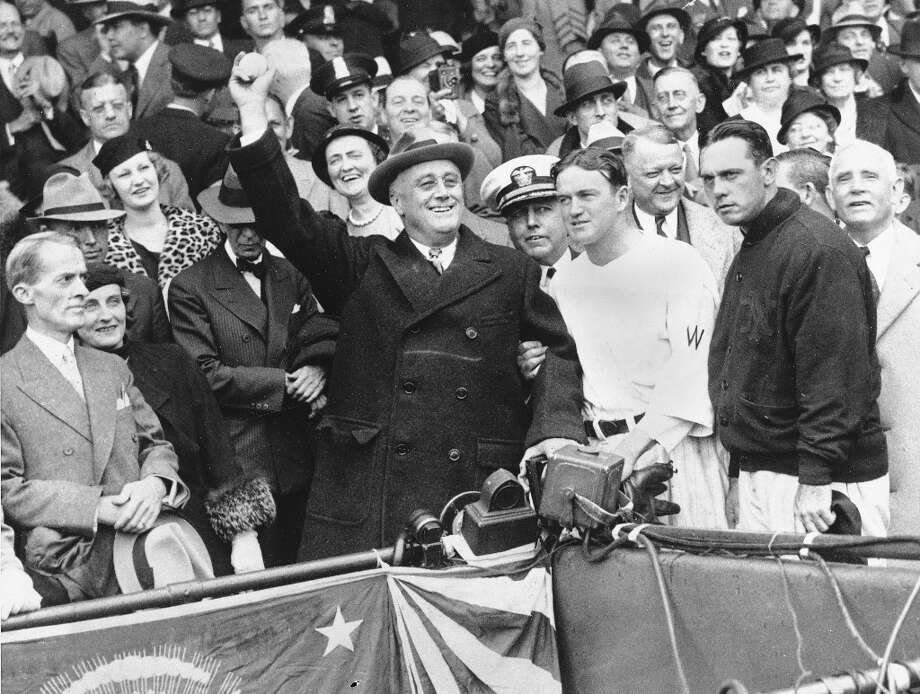 In this Oct. 5, 1933 file photo, President Franklin D. Roosevelt prepares to throw out the ceremonial first pitch at Griffith Stadium in Washington before Game 3 of the World Series. Washington Senators manager Joe Cronin, third from right, and New York Giants manager Bill Terry, second from right, look on. Newspapers noted the President uncorked a wild throw that sent the players scrambling. Photo: Associated Press / AP