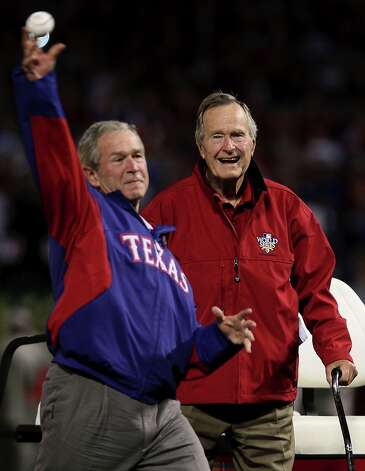 George W. Bush, throws out the first pitch as his father George H.W. Bush looks on (and possibly laughs at his son's technique). Photo: Elsa, Getty Images / 2010 Getty Images