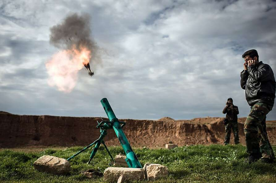 TOPSHOTS Syrian rebels fire a mortar towards regime forces stationed at Kwiriss airport in Al-Bab, 3