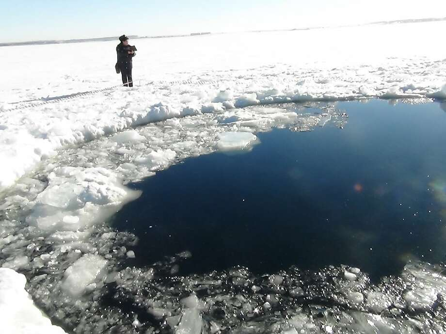 Authorities believe an estimated 7,000-ton meteor that created a panic in Chelyabinsk, Russia, crashed into nearby Chebarkul Lake and produced this circular hole. Photo: Associated Press