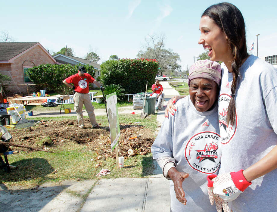 Flossie Lewis, left, president of the Foster Place Community Civic Club, hugs WBNA New York Liberty player Nicole Powell during the Rebuilding Together Home Refurbishments. Photo: Melissa Phillip, Houston Chronicle / © 2013 Houston Chronicle
