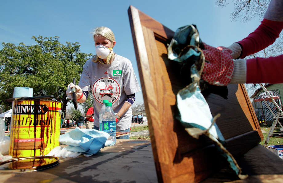 Liz Criqui, left, of Ridgewood, NJ and Lesile Nguyen, right, of Houston work to stain cabinets outside a home in the Foster Place Community as part of Rebuilding Together Home Refurbishments. Photo: Melissa Phillip, Houston Chronicle / © 2013 Houston Chronicle