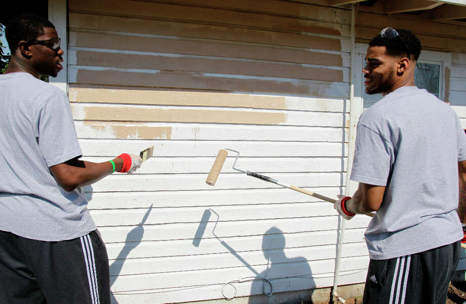 NBA D-League BayHawks players Henry Sims, left, and D. J. Kennedy, right, paint a home in the Foster Place Community. Photo: Melissa Phillip, Houston Chronicle / © 2013 Houston Chronicle