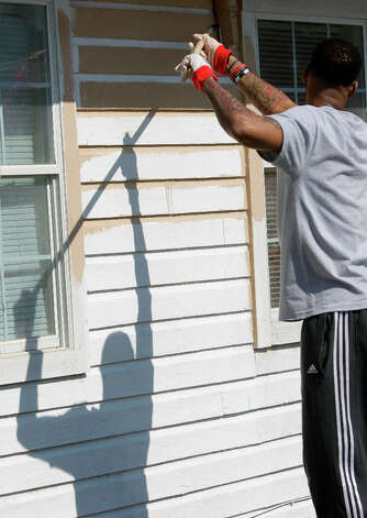 NBA D-League BayHawks player D. J. Kennedy paints a home in the Foster Place Community as part of Rebuilding Together Home Refurbishments. Photo: Melissa Phillip, Houston Chronicle / © 2013 Houston Chronicle