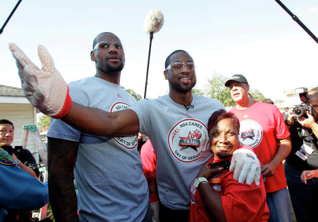 NBA players LeBron James, left, and Dwyane Wade, center, talk with homeowner Myrteal Gray outside her Foster Place Community home. Photo: Melissa Phillip, Houston Chronicle / © 2013 Houston Chronicle