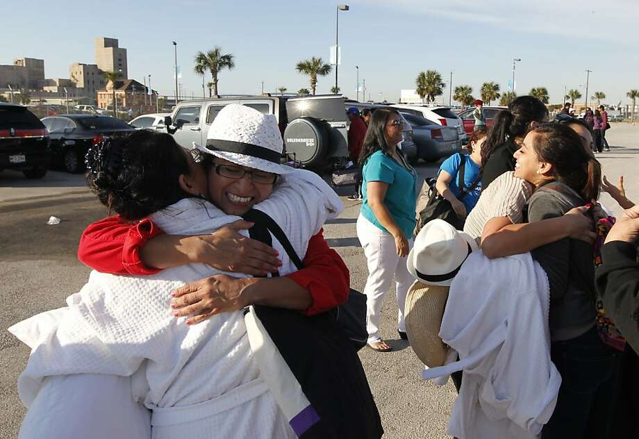 Patricia Wagner, right, hugs her sister Mercedes Perez de Colon,as their group is reunited after taking separate buses from Mobile, Ala., where the disabled Carnival ship Triumph docked, on Friday February 15, 2013 in Galveston, Texas. Hundreds of passengers opted to take an eight-hour bus ride to Galveston from Mobile.  Galveston is the home port of the ill-fated ship, which lost power in an engine-room fire Sunday some 150 miles off Mexico's Yucatan peninsula. Photo: Jennifer Reynolds, Associated Press