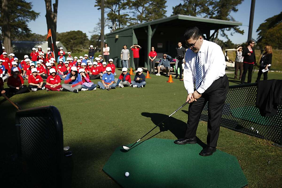 SFUSD Supervisor Richard Carranza prepares to hit a long drive as Lawton Alternative School fifth graders watch during a