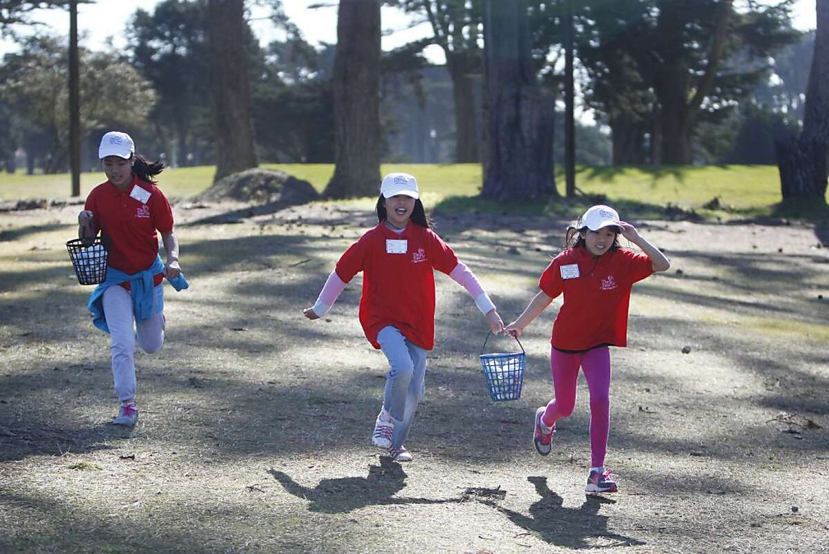"""Lawton Alternative School fifth graders Dana Hu (l to r), 10; Sammi Situ, 11; and Maggie Mah, 10 run back to their station after collecting balls while practicing their long drive during a """"First Tee"""" golf class at TPC Harding Park on Friday, February 15, 2013 in San Francisco, Calif."""