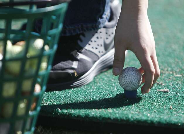 "Lawton Alternative School  fifth graders Justin Li, 10, places a golf ball on a tee while practicing chipping during a ""First Tee"" golf class at TPC Harding Park on Friday, February 15, 2013 in San Francisco, Calif. Photo: Lea Suzuki, The Chronicle"