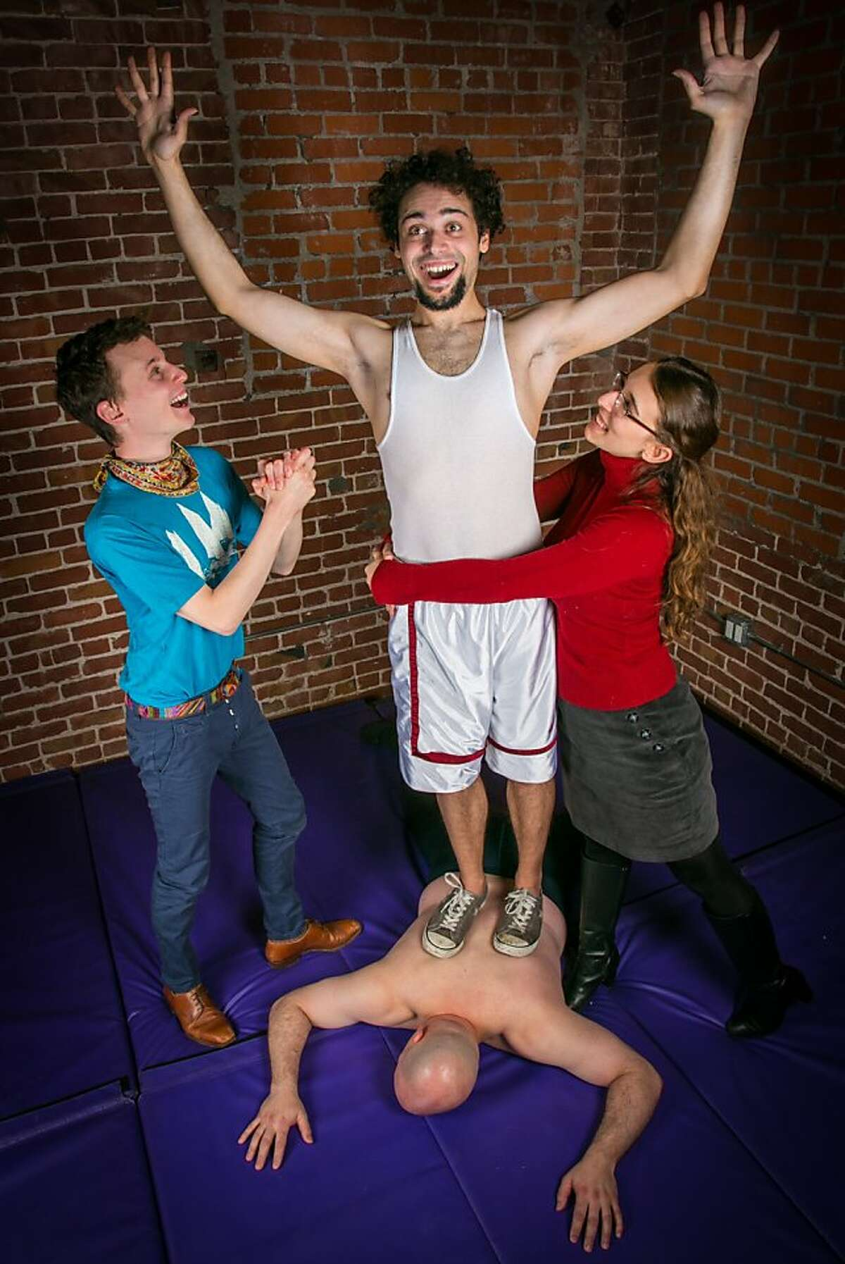 """Orlando (Miyaka Cochrane, center) bests the famous wrestler Charles (Stacz Sadowski) as Rosalind (Maria Giere Marquis) and Celia (Alexander Lenarsky) celebrate his short-lived victory in Impact Theatre's even-more-gender-bending-than-usual """"As You Like It,"""" running through March 30 at LaVal's Subterranean in Berkeley."""
