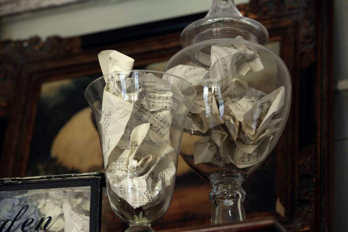 Large glass jars atop the wardrobe hold vintage sheet music.