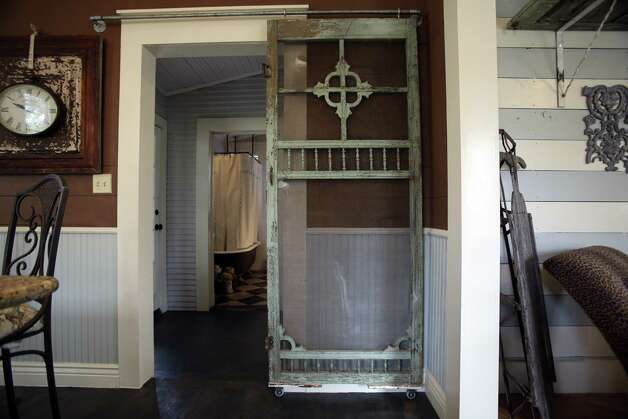 An old screen door slides from a pipe to separate the kitchen from the hall.
