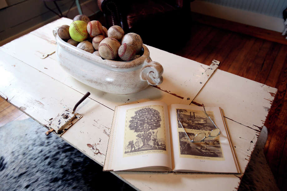 The coffee table in the living room of Shane and Jayme Boscamp is accessorized with a bowl of baseballs and softballs and a book. Photo: Helen L. Montoya, San Antonio Express-News / ©2013 San Antonio Express-News