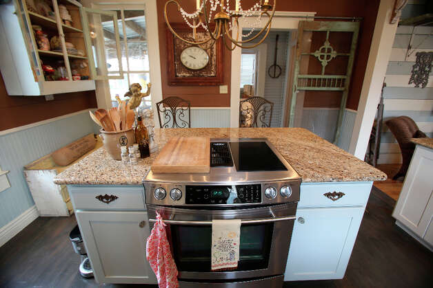 Shane and Jayme Boscamp painted dark cabinets white to give space and light to the kitchen and added granite counters and renovated the island when they bought the house in 2011. Photo: Helen L. Montoya, San Antonio Express-News / ©2013 San Antonio Express-News