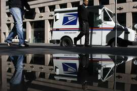 Passersby walk past a mail truck in front of the Rincon Center postal office on Friday, Feb. 13. The Postal Service is planning to cut Saturday services completely.
