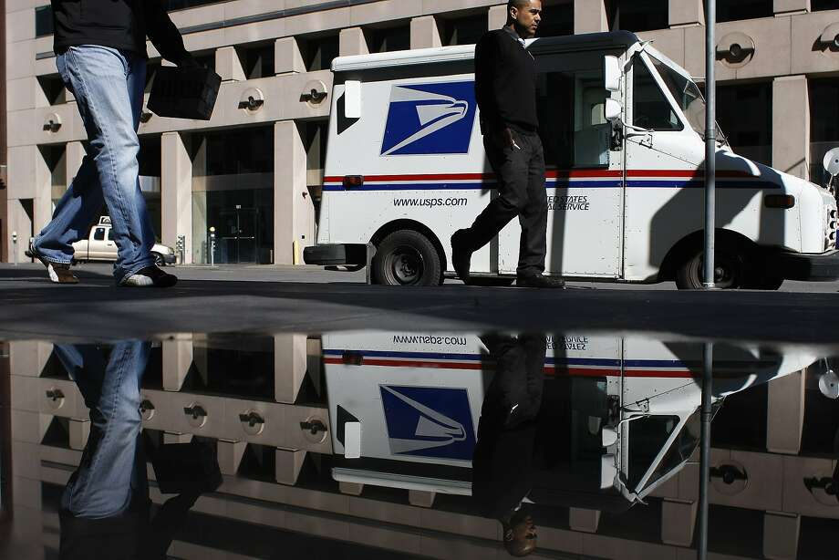 Passersby walk past a mail truck in front of the Rincon Center postal office on Friday, Feb. 13. The Postal Service is planning to cut Saturday services completely. Photo: James Tensuan, The Chronicle
