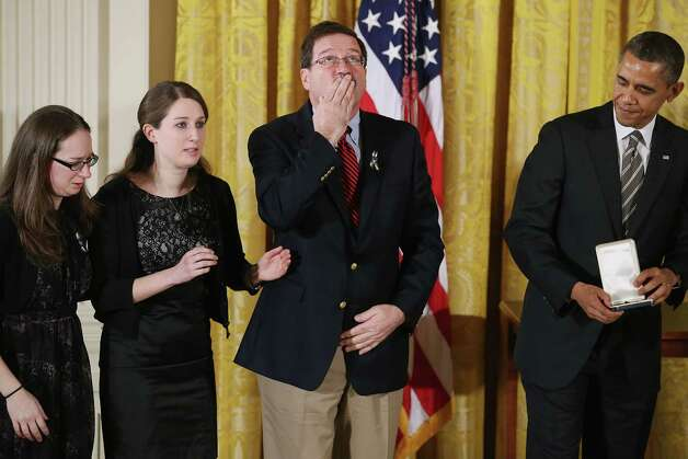"Bill Sherlach blows a kiss skyward as U.S. President Barack Obama presents him and daughters Katy Sherlach and Maura Lynn Schwartz with the 2012 Presidential Citizens Medal, the nation's second-highest civilian honor, on behalf of their wife and mother Mary Sherlach in the East Room of the White House February 15, 2013 in Washington, DC. School psychologist Mary Sherlach was killed during a mass shooting that left 26 people dead at Sandy Hook Elementary School in December 2012. ""Their selflessness and courage inspire us all to look for opportunities to better serve our communities and our country,"" Obama said about this year's recepients. Photo: Chip Somodevilla, Photo By Chip Somodevilla/Getty / 2013 Getty Images"