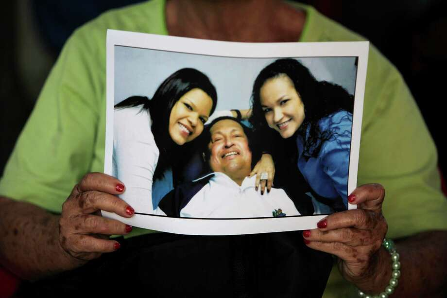 A man holds a print of one of the photographs released Friday by the government showing President Hugo Chavez with his daughters Maria Gabriela, left, and Rosa Virginia, right, at Bolivar square in Caracas, Venezuela, Friday, Feb. 15, 2013.   Amid widespread speculation and rumors in Venezuela about Chavez's delicate condition following his Dec. 11 cancer surgery, the government released the first photos of the ailing president in more than two months on Friday, presenting images of him smiling alongside his daughters in Cuba. (AP Photo/Fernando Llano) Photo: Fernando Llano
