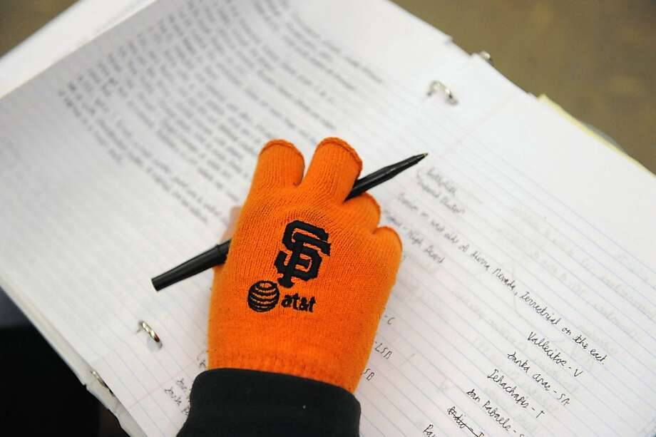 Student Matthew Innes wears his Giants orange gloves while taking notes in Mark Sigmon's class on the history and literature of baseball at San Francisco State University. Photo: Susana Bates, Special To The Chronicle