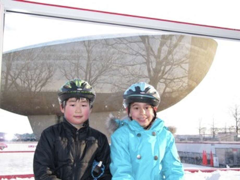"Benjamin and Amelia Lynk take a break from skating at Empire State Plaza while the ice is being cleared by a Zamboni. "" When we looked at the picture later we were surprise by the refection  of the trees on the Egg,"" says Charley Lynk. (Charley Lynk)"