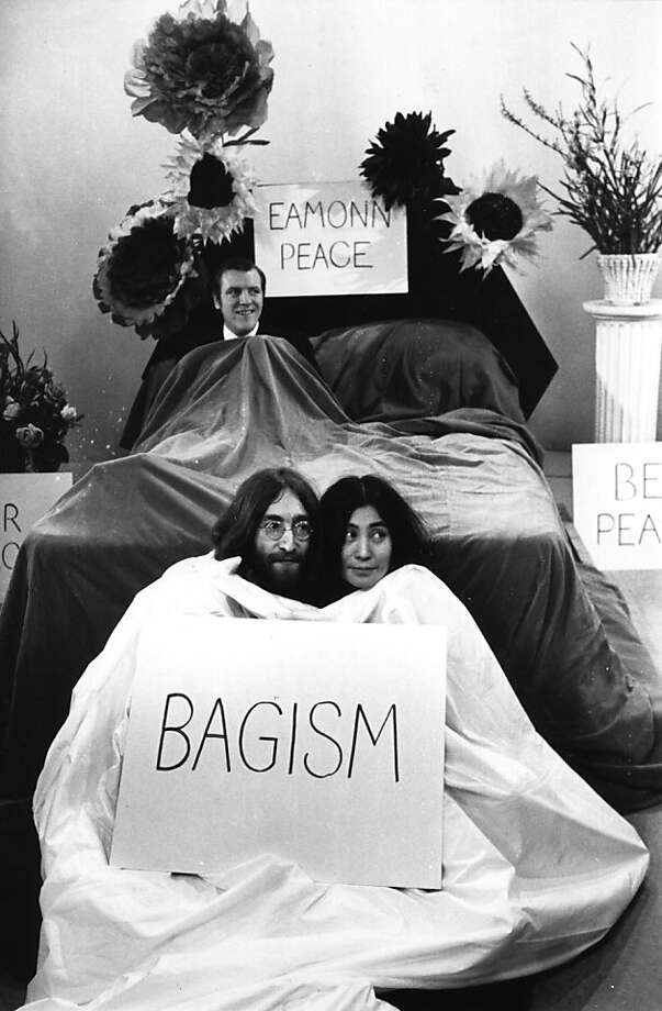 John Lennon and his wife Yoko Ono sit in a bag before appearing on the 'Today' program with Eamonn Andrews, seen in  bed in the background.  Photo: Bob Aylott