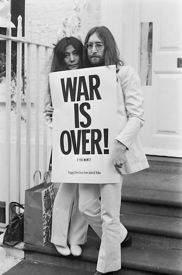 John Lennon and Yoko Ono pose on the steps of the Apple building in London, holding one of the posters that they distributed to the world's major cities as part of a peace campaign protesting against the Vietnam War, December 1969. The poster reads 'War Is Over, If You Want It'. (Photo by Frank Barratt/Keystone/Getty Images) Photo: Frank Barratt