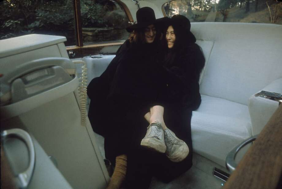 Japanese-born artist and musician Yoko Ono and British musican and artist John Lennon, both dressed in black, clown around in the back seat of an all-white white luxury car, December 1968. Photo: Susan Wood/Getty Images