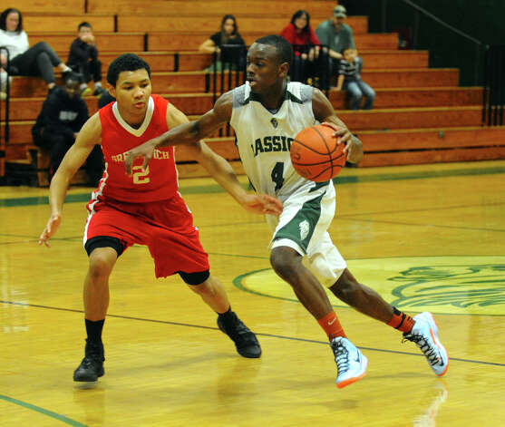 Bassick's #4 Kobe Ancrum drives past Greenwich's #2 C.J. Byrd, during boys basketball action in Bridgeport, Conn. on Friday February 15, 2013. Photo: Christian Abraham / Connecticut Post