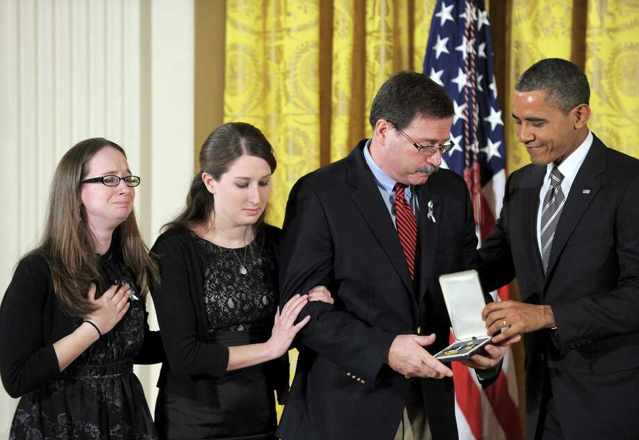 US President Barack Obama presents a Citizens Medal to the family  of Sandy Hook Elementary School psychologist Mary Sherlach on February 15, 2013 during a ceremony in the East Room of the White House in Washington. Photo: JEWEL SAMAD, AFP/Getty Images / AFP