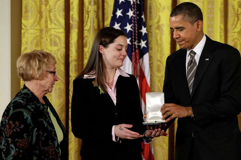 President Barack Obama presents a 2012 Citizens Medal to the family of Sandy Hook Elementary School Principal Dawn Hochsprung, daughter Erica Lafferty and mother Cheryl Lafferty, Friday, Feb. 15, 2013, in the East Room of the White House in Washington. Photo: Jacquelyn Martin, Associated Press / AP