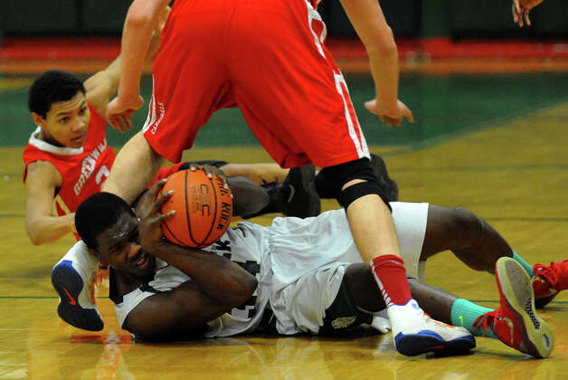Bassick's #34 Dale Kirkland attempts to hang onto the ball as Greenwich's #32 Alex Wolf and #2 C.J. Byrd, back left, converge, during boys basketball action in Bridgeport, Conn. on Friday February 15, 2013. Photo: Christian Abraham / Connecticut Post