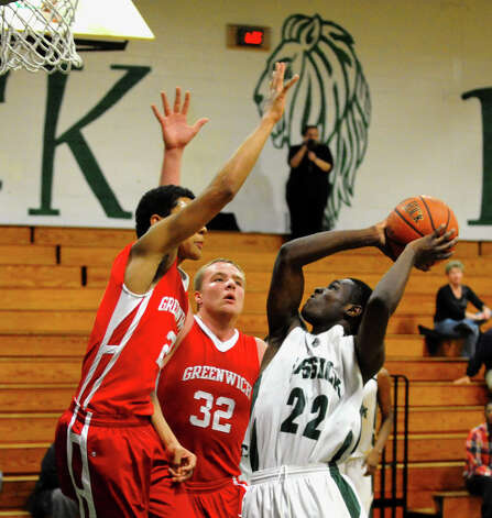 Bassick's #22 David Steele attempts a shot as Greenwich's #32 Alex Wolf and #2 C.J. Byrd, left, defend, during boys basketball action in Bridgeport, Conn. on Friday February 15, 2013. Photo: Christian Abraham / Connecticut Post