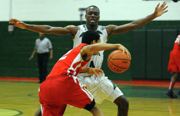 Bassick's #4 Kobe Ancrum blocks a drive by Greenwich's #2 C.J. Byrd, during boys basketball action in Bridgeport, Conn. on Friday February 15, 2013. Photo: Christian Abraham / Connecticut Post
