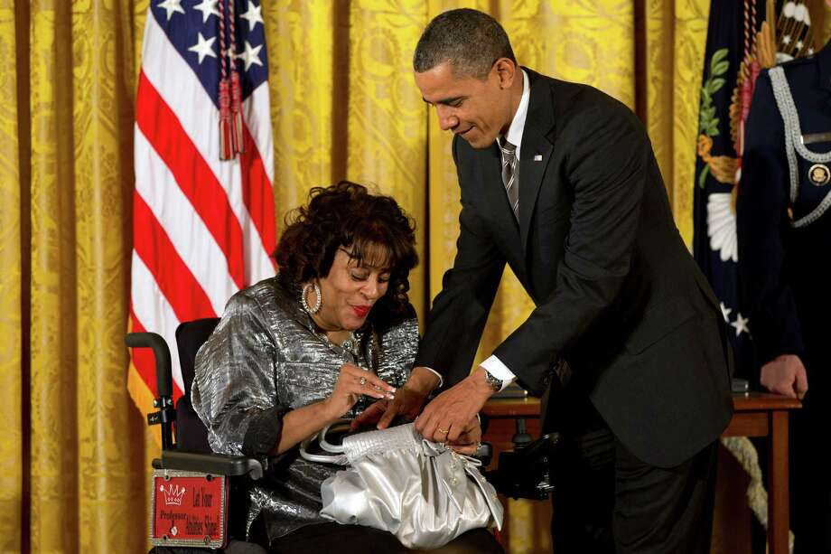 President Barack Obama helps put a 2012 Citizens Medal into the purse of Janice Jackson of Baltimore, Friday, Feb. 15, 2013, during a ceremony in the East Room of the White House in Washington. Jackson is the creator and program director of Women Embracing Abilities Now, (W.E.A.N.) a nonprofit mentoring organization servicing women and young ladies with varying degrees of disabilities. Photo: Jacquelyn Martin, Associated Press / AP