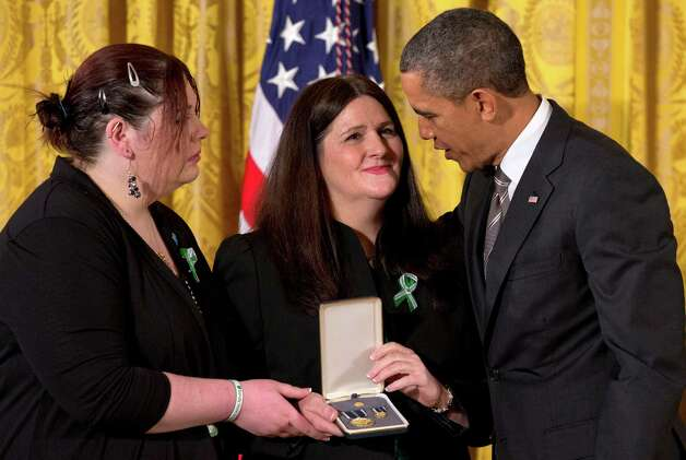 President Barack Obama presents a 2012 Citizens Medal to the family of slain Sandy Hook Elementary School teacher's aide Rachel Davino, Friday, Feb. 15, 2013, in the East Room of the White House in Washington. Photo: Jacquelyn Martin, Associated Press/Jacquelyn Marti / Associated Press