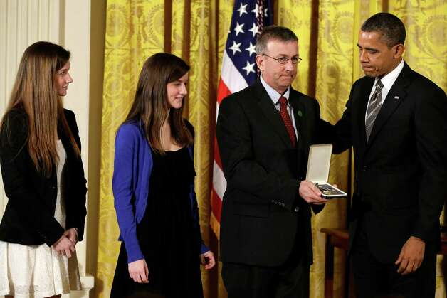 President Barack Obama presents a 2012 Citizens Medal to the family of slain Sandy Hook Elementary Schoolteacher Anne Marie Murphy, Friday, Feb. 15, 2013, in the East Room of the White House in Washington. Photo: Jacquelyn Martin, Associated Press/Jacquelyn Marti / Associated Press
