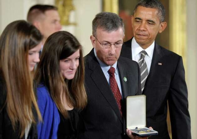 The family of slain Sandy Hook Elementary School teacher Anne Marie Murphy, daughters Paige and Colleen Murphy, and her husband Michael Murphy, accepts the 2012 Presidential Citizens Medal, the nationís second-highest civilian honor, on her behalf posthumously from President Barack Obama, Friday, Feb. 15, 2013, during a ceremony in the East Room of the White House in Washington. Photo: Susan Walsh, AP Photo/Susan Walsh / AP2013 Associated Press